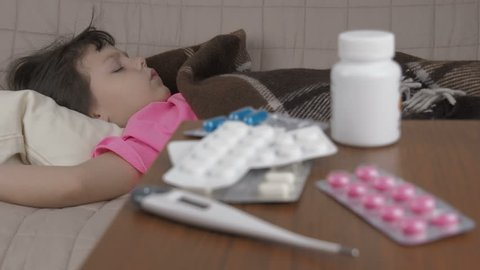 CLose-up view of pills and thermometer. In background child sleeping.