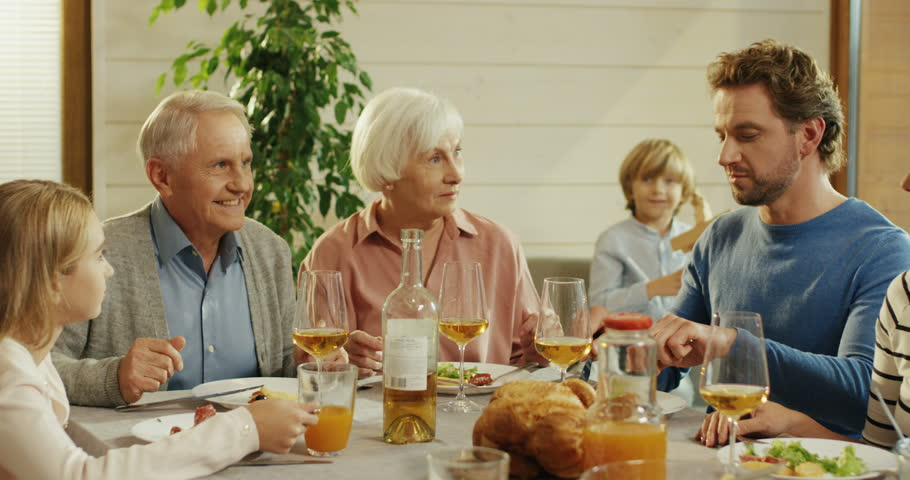 Senior couple of parents having a dinner with their son, daughter-in-law and two grandchildren at home. | Shutterstock HD Video #1021141516