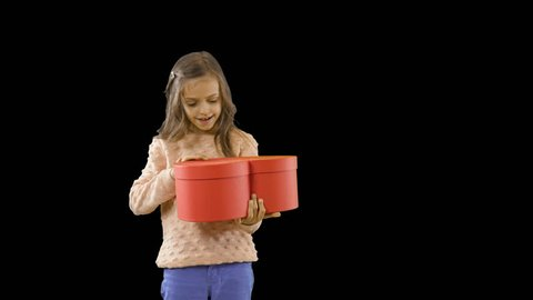 Delight of a little girl who holds a red box in the shape of a heart in her hands opens it and rejoices smiling and opening her mouth wide, emotions, baby shooting, shooting on an isolated background