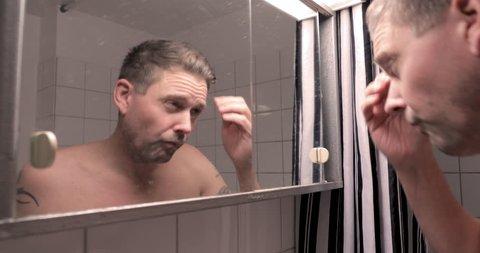 Man admires himself whilst looking into bathroom mirror