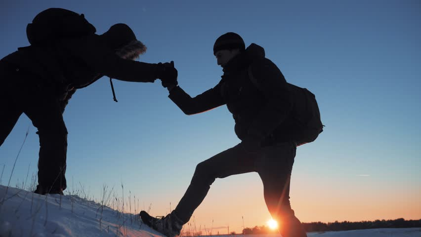 Teamwork business travel silhouette concept. two hikers winter snow tourists climbers climb to the top of mountain . overcoming hardships lifestyle the path to victory, teamwork, important points in | Shutterstock HD Video #1021163566