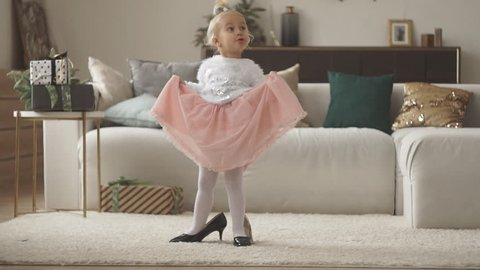 Pretty little girl in mom's shoes. Small fashionista trying on high heels at home