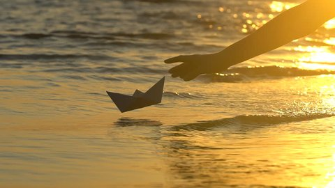 Kid child putting paper boat into water reflection of sun over beautiful sunset Male child's hand launches paper ship on sea surface Ship sailing Dreams future childhood freedom childhood hope concept