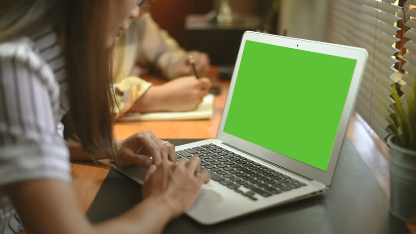 Asian woman works on a Laptop with Mock-up Green Screen  | Shutterstock HD Video #1021238866