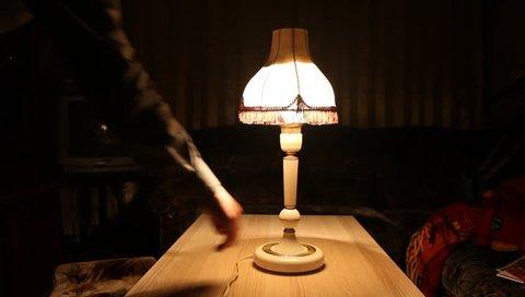 Vintage sensor floor lamp (made in USSR in 80s) in room of soviet flat. Man lights on  and lights off lamp
