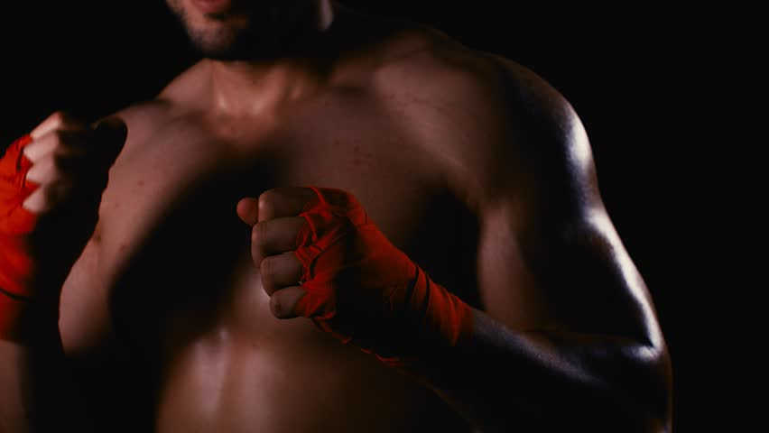 Male boxer with wrapped hands fight training process on black background #1021363336