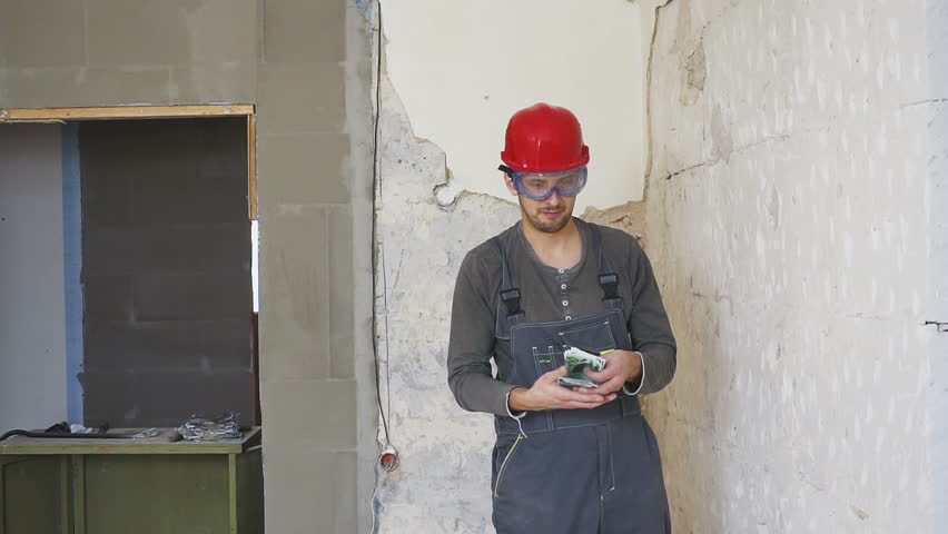 The worker in a construction with helmet counts money euro against the background of the repaired apartment. | Shutterstock HD Video #1021367656