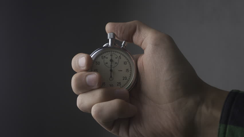 Close-up of one person starting up a stopwatch at grey background. 4K, 10 BIT, 4:2:2.   Shutterstock HD Video #1021395286