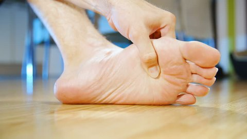 Massaging painful foot by hand slow motion HD. Low angle long shot of person's foot in focus while massaging with a hand at home. Background dining room out of focus.