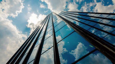 4K 30p Huge,tall glass skyscraper dramatic sun and dark clouds reflection timelapse.Beautiful thick white summer clouds and sun with light rays reflected on the surface of a big corporate building.