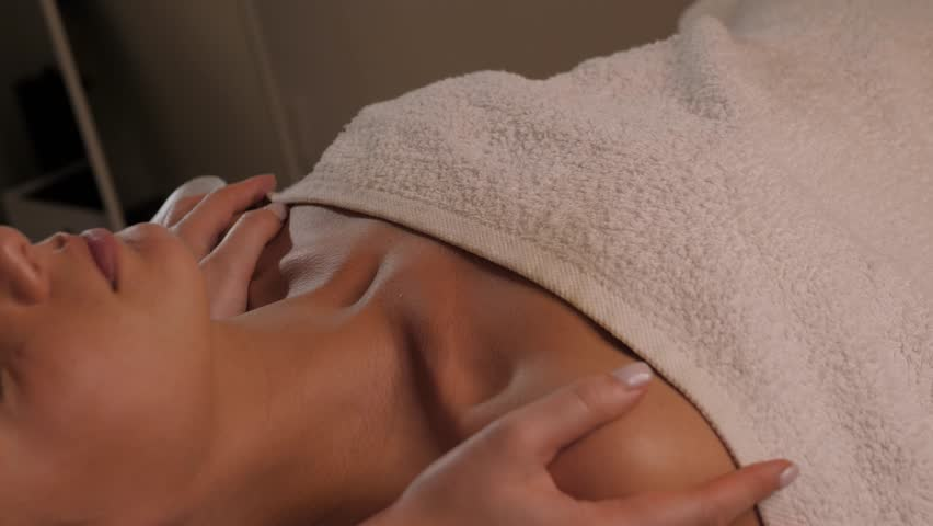 Masseur doing massage the head of an young beautiful girl woman in the spa salon close up macro | Shutterstock HD Video #1021441906