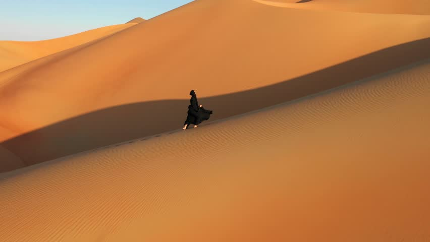Aerial view from a drone following a young woman in traditional black abaya walking on massive sand dunes in the Empty Quarter desert. Abu Dhabi, UAE.