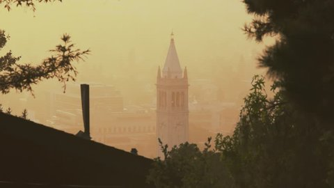 UC Berkeley Campanile drenched in golden sunset, seen from above campus on the fire trails in Berkeley, California, close up