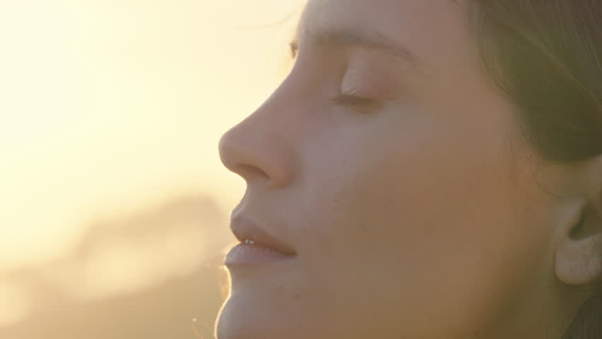 close up portrait of beautiful woman enjoying peaceful sunset exploring spirituality looking up praying contemplating journey with wind blowing hair #1021487026