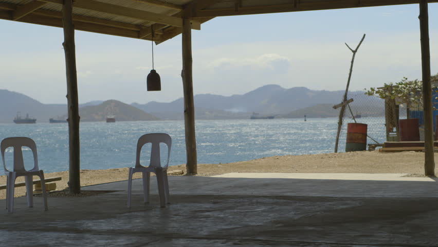A shot of beach shack with plastic chairs with sea and ships in background in Papua new guinea