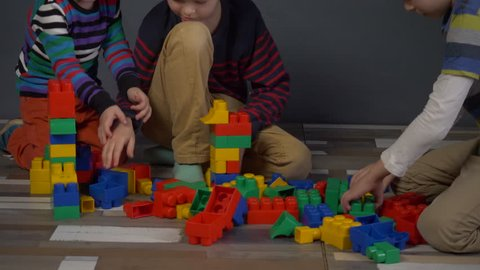 Cute children preschoolers play in color cubes, blocks. Boys are actively building new forms and expressing their emotions. Brothers study and get ready for school. Kids are happy to play together