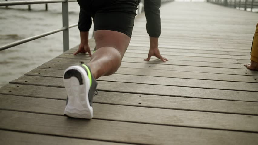 Rear view of muscular man stretching legs. African american sportsman warming up on wooden pier. Sport concept | Shutterstock HD Video #1021517326