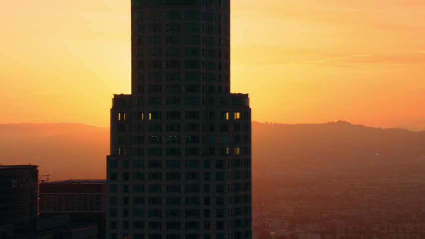 Soaring near high rise buildings around downtown Los Angeles at sunset. Aerial wide shot filmed with a RED camera.