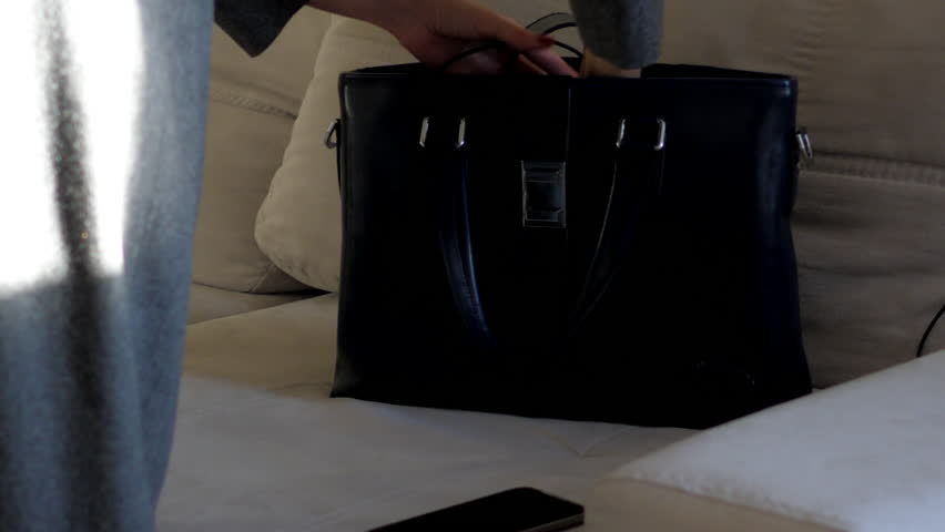 Close view young woman puts mobile phone into small black handbag on white sofa in living room | Shutterstock HD Video #1021528966