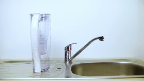 Filling up the filter with tap water HD. Wide shot of water filter pitcher in focus on a kitchen sink. White background.