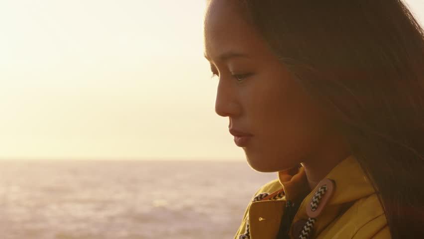 Portrait of beautiful asian woman enjoying seaside at sunset exploring spirituality looking up praying contemplating journey relaxing on beach | Shutterstock HD Video #1021561006
