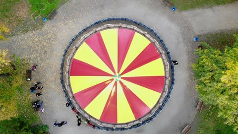 CHERKASY, UKRAINE, OCTOBER 17, 2018: Colourful, red and yellow carousel, a carnival Merry Go Round, in the autumn park, aero, view from above.