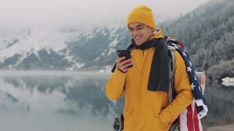 American traveler man using smartphone in hiking winter tour. Snowy lake and mountains against background. Traveling and communication concept: hiker scrolling and tapping on line by cell phone