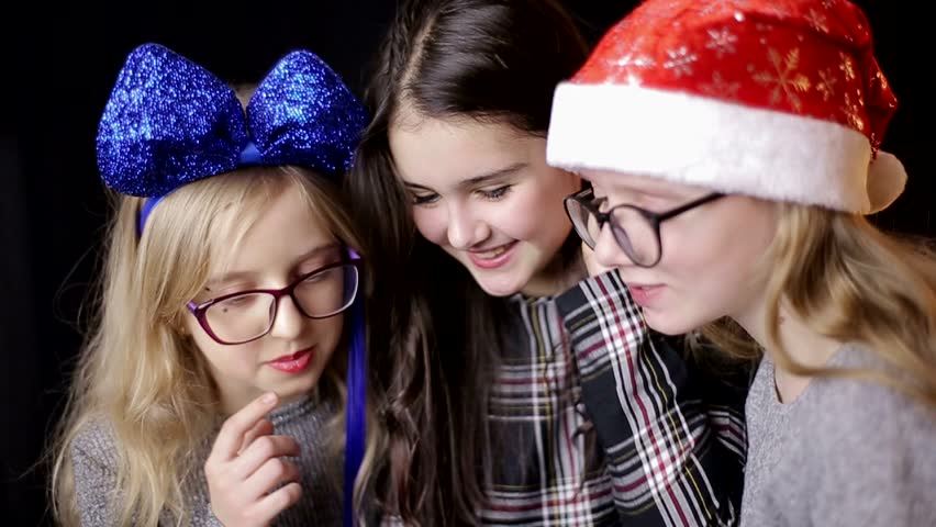 Three teenage girls on a black background, playing games on the phone. Dependency on gambling   Shutterstock HD Video #1021671766