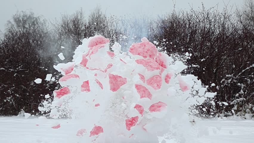 Pink coloured snowball in shape of heart smoke and explode, break apart, super slow motion shot. Small pieces slowly fly round and down, cloud of smoke dissolve in air