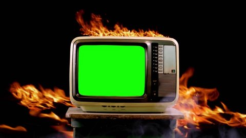 "Old TV with Green Screen On Fire Background. Ready to Replace Green Screen with any Footage or Picture you Want. You can do it with ""Keying"" (Chroma Key) effect in AE Effects or other Software."