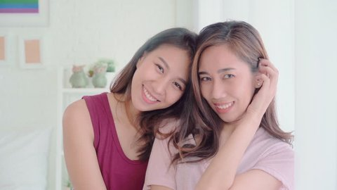 Young Asian women lesbian happy couple smiling and looking to camera while relax in her bedroom at home. Beautiful female using relax time at home. Lifestyle LGBT couple together indoors concept.