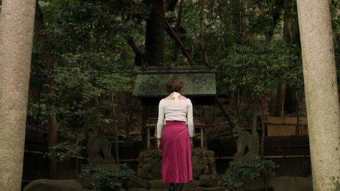 Wide shot on 4k RED camera of somber Japanese woman walking up to a shrine and bowing towards it in a beautiful garden with soft natural lighting.