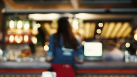 Blurred image of the interior of a large beautiful restaurant with bright lighting. The waitress comes to the working bar and the bartender, gives visitors a menu and goes for a drink. Defocused staff