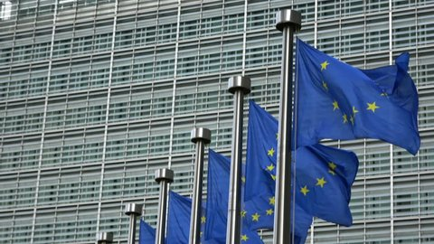 4K. European Union flags waving in front of Berlaymont Building in Brussels, headquarter of the European Commission