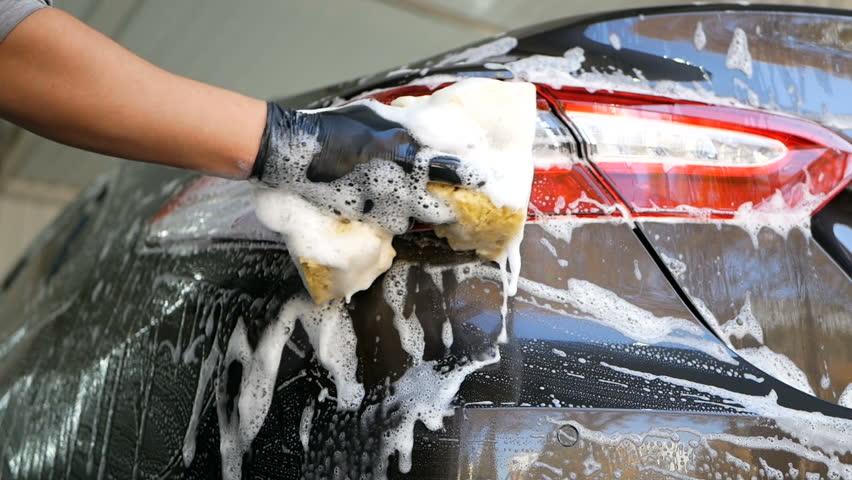 Close up male hand in black glove with foam sponge washing car headlight. bottom view. Concept: Auto Car Service, Car Wash | Shutterstock HD Video #1021858516