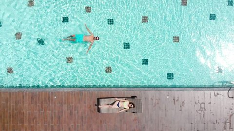 A man swims in the pool outdoors, next to the chaise longue is a beautiful girl in a swimsuit and sunbathing. Relax, rest or vacation on the roof of a luxury hotel. Aerial Top view
