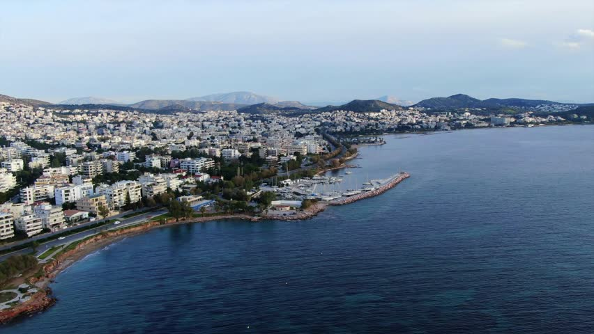 Aerial drone bird's eye view video of famous seascape of Athens Riviera at sunset, Voula, Attica, Greece #1021894996