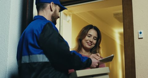 Rear of the Caucasian pizza deliveryman in blue uniform ringing in the doorbell, beautiful woman opening a door, signing and taking her order. Indoor.