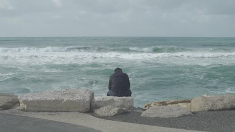 Old man sits on the rocks of a beach promenade while waves crash in BG