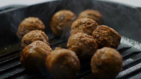 chef fry raw meatballs in iron pan on hot stove for steak dinner meal. Seamless cinemagraph video
