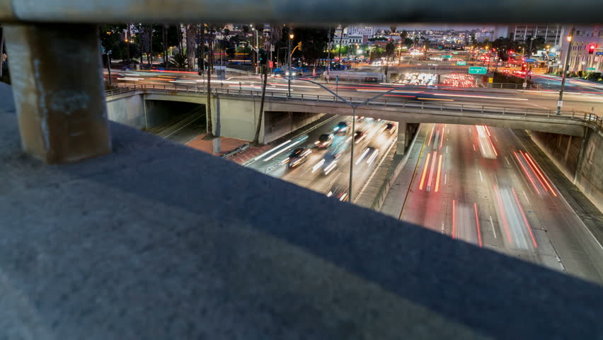 Freeway Traffic Time-lapse. Tracking shot moving along a freeway overpass looking down on traffic speeding by. | Shutterstock HD Video #1021933846