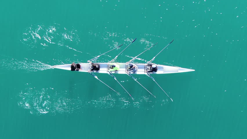 Aerial drone bird's eye view video of sport canoe operated by team of young women in turquoise clear waters #1021950076