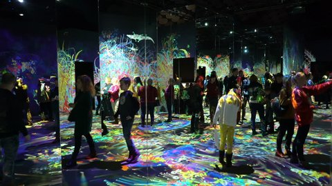 "HELSINKI, FINLAND - JAN 06, 2019: ""Massless"" Exhibition - immersive interactive graphic digital installations by Japanese artists TeamLab at Amos Rex Museum. Visitors enjoy the new modern digital art."