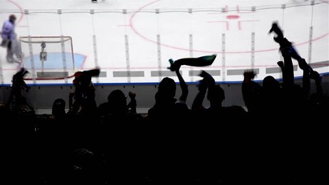 Silhouettes of fans rejoice at a goal in hockey.