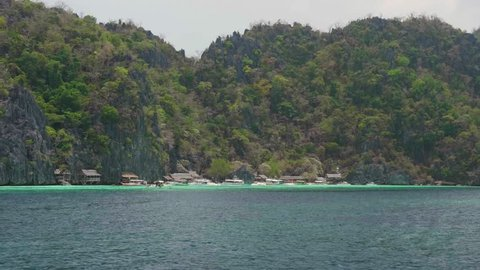 Small Houses On A Beach In A Tropical Archipelago With Permian Limestone Mountains, Steep Cliffs And Turquoise Water.