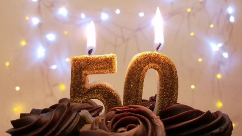Burning birthday candle on a birthday cake. Number 50, blow out at the end. Color blurred background.