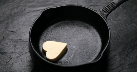 Fried butter, a piece of butter in the shape of hearts, fried on a black cast-iron pan. Impression about a healthy heart, anti cholesterol prophylaxis, healthy heart concept, 4k