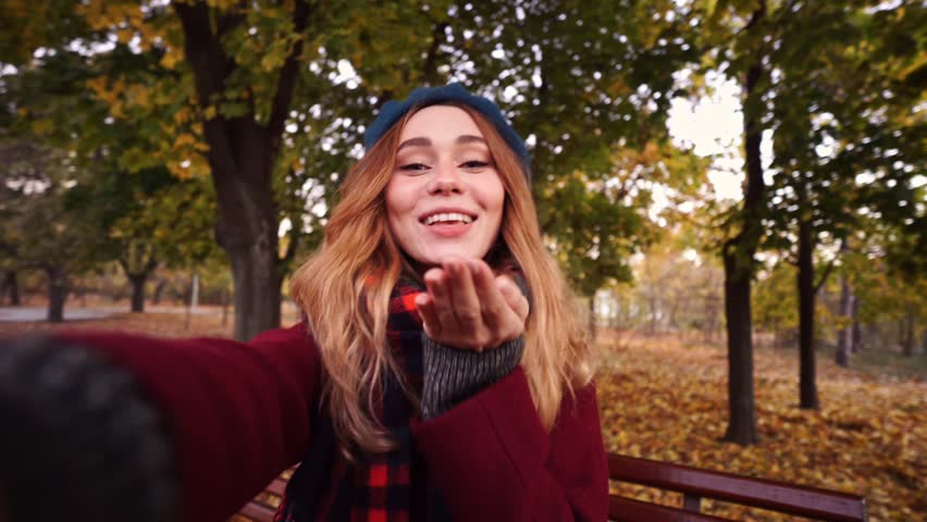 14336ab4518c3 Happy brunette woman in beret hat and coat making selfie while sitting on  bench in park