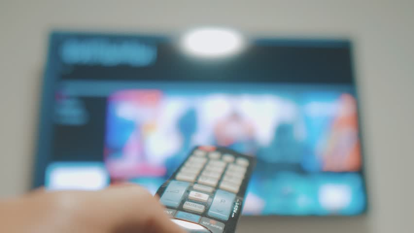 Smart tv with apps and hand. Male hand holding the remote control turn off smart tv lifestyle . man hand controls TV holding remote. concept internet online cinema | Shutterstock HD Video #1022107336
