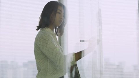 Focused Japanese woman writing an equation with a marker on glass and problem solving in a contemporary office with bright natural lighting. Medium to close up shot on 4k RED camera.